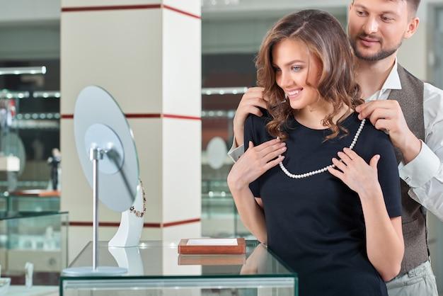 Jovem ajudando a namorada a ajustar o colar no je