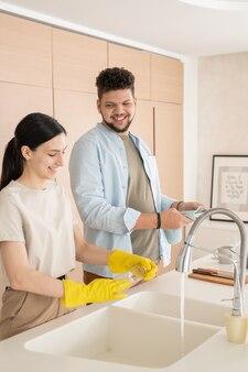 Jovem ajudando sua esposa a lavar pratos após o café da manhã