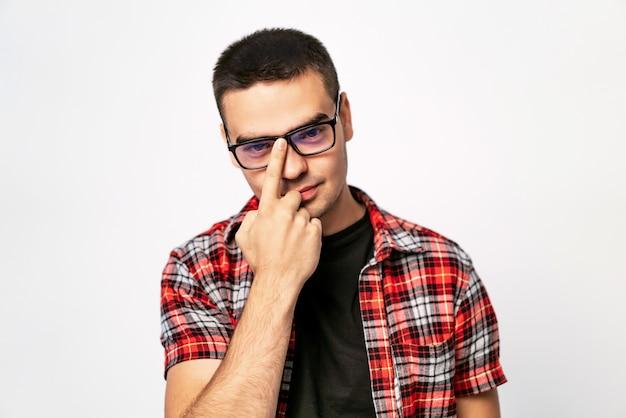Jovem, ajustando os óculos que ele usa com um sorriso isolado no branco