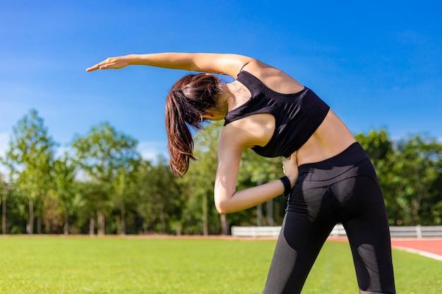 Jovem, ajustar, mulher asian, esticar, dela, corporal, durante, dela, exercício manhã, em, um, ao ar livre, pista de atletismo