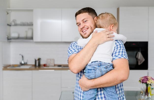 Jovem alegre abraçando uma criança