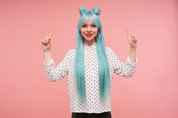 Jovem alegre adorável de cabelos azuis, vestida com uma camisa branca com pontos pretos olhando positivamente e levantando os indicadores