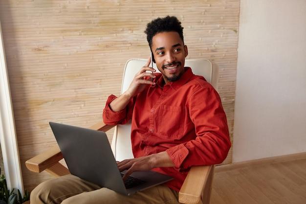 Jovem alegre adorável homem barbudo de cabelos curtos e pele escura sorrindo amplamente para o lado enquanto faz uma ligação, trabalhando remotamente de casa, isolado em bege