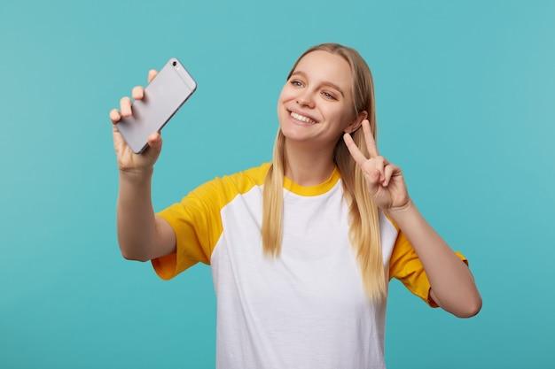 Jovem alegre adorável loira de cabelos compridos mostrando um gesto de vitória ao fazer um retrato de si mesma no celular, posando em azul no uso casual