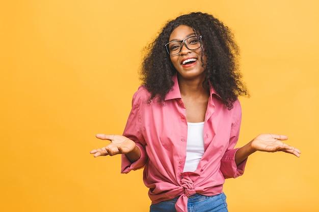 Jovem alegre afro-americana com cabelo encaracolado e um sorriso feliz.