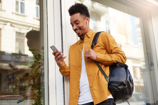 Jovem alegre afro-americano de camisa amarela, parece feliz e amplamente sorridente, andando pela rua e segura o telefone, conversando com amigos.