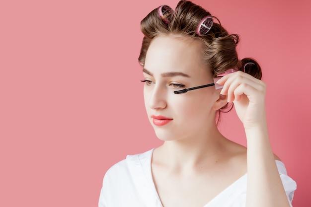 Jovem alegre agradável a menina no encrespador pinta uma sobrancelha em fundo rosa