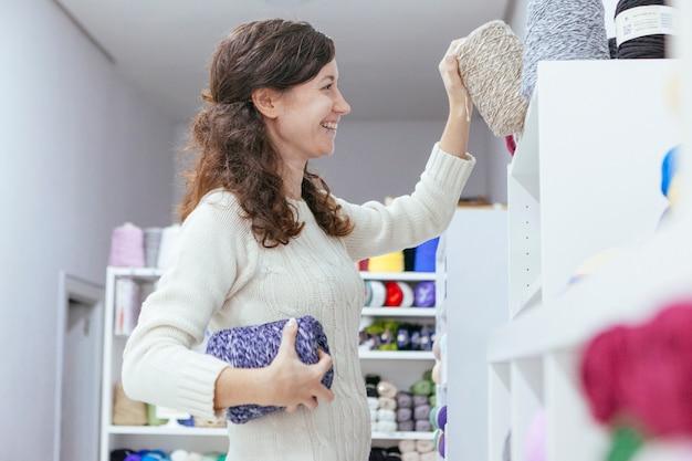 Jovem alegre alegre organizando fios de lã em seu próprio negócio de arte
