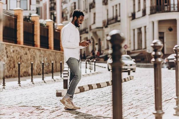 Jovem alegre andando na rua e usando um smartphone moderno