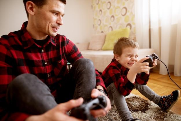 Jovem alegre animado pai e filho com a mesma camisa vermelha, jogando jogos de console com gamepads em uma luminosa sala de estar.