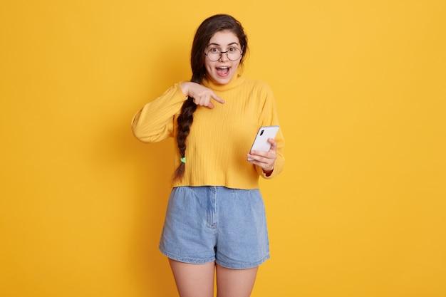 Jovem alegre apontando para o telefone inteligente na mão com expressão facial animada, mantém a boca aberta, vestindo suéter e curto, garota com longos cabelos escuros e trança.