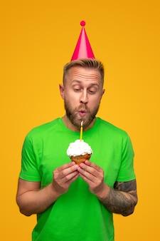 Jovem alegre barbudo com uma camisa verde brilhante e um chapéu de festa soprando uma vela no bolinho doce com creme chantilly durante a celebração do aniversário