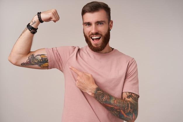 Jovem alegre barbudo homem moreno com corte de cabelo da moda, vestindo uma camiseta bege, posando em branco, mostrando sua mão levantada e sentindo-se orgulhoso de seus músculos fortes