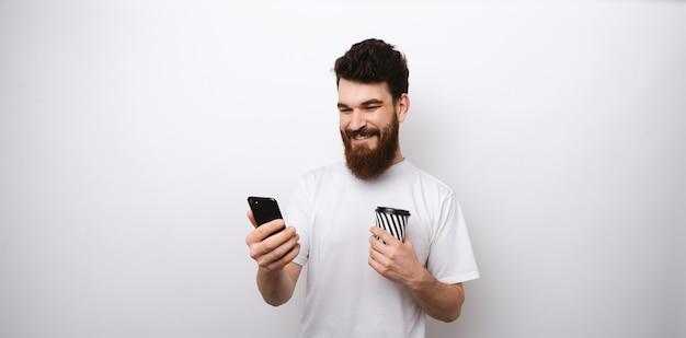 Jovem alegre barbudo homem olhando no telefone, navegar na internet, fazer um selfie e segurando uma xícara de chá ou café.