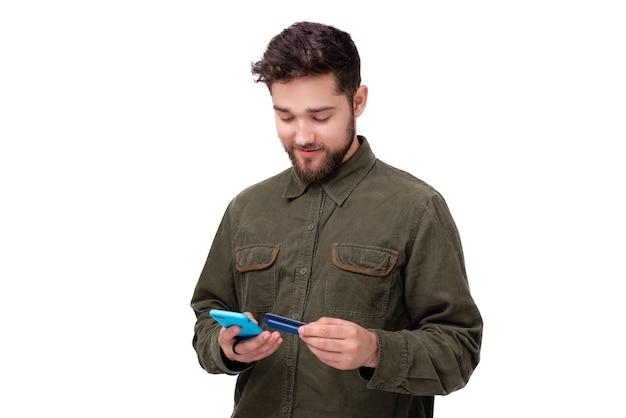 Jovem alegre barbudo usando um telefone celular e um cartão de crédito na parede com fundo branco