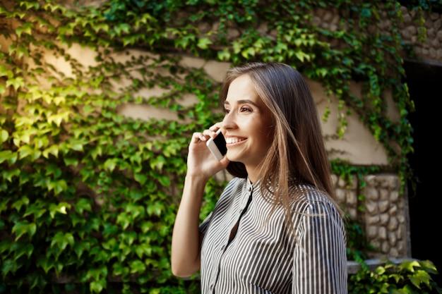 Jovem alegre bonita andando pela cidade, falando no telefone.
