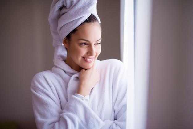 Jovem alegre bonita em um roupão com uma toalha em volta do cabelo está sorrindo e se sentindo fresca depois do banho enquanto olha pela janela e se sente confortável.
