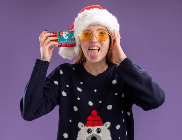 Jovem alegre bonita vestindo suéter de natal e chapéu com óculos segurando o copo de natal na orelha e mostrando a língua isolada no fundo roxo