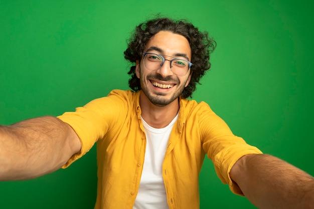 Jovem alegre, bonito, caucasiano, usando óculos, olhando para a câmera, estendendo as mãos em direção à câmera, isolado no fundo verde
