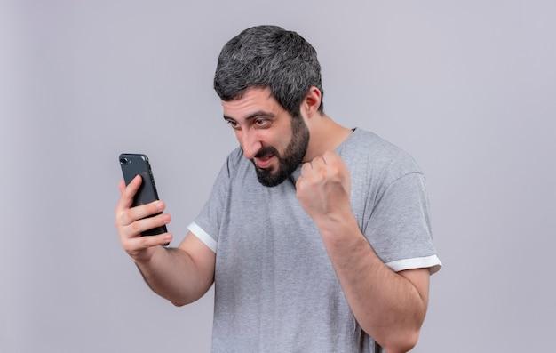Jovem alegre bonito homem branco segurando e olhando para o celular e levantando o punho isolado no branco