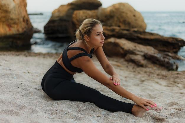 Jovem alegre cabe mulher fazendo alongamento de pernas, sentado na areia na praia selvagem
