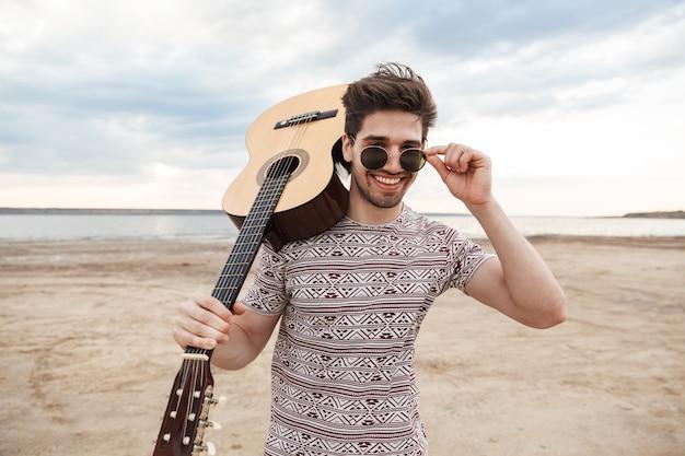 Jovem alegre carregando um violão, em pé na praia