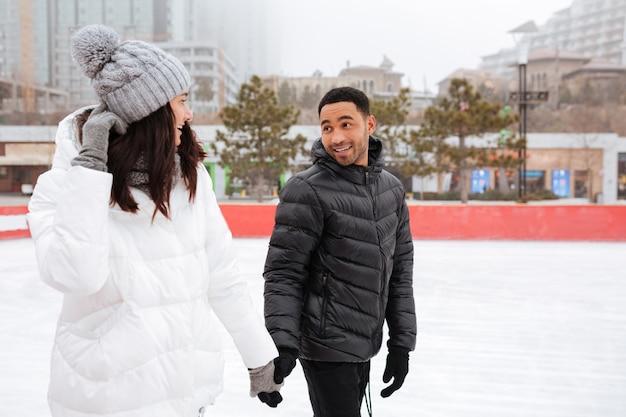 Jovem alegre casal apaixonado patinar na pista de gelo ao ar livre.