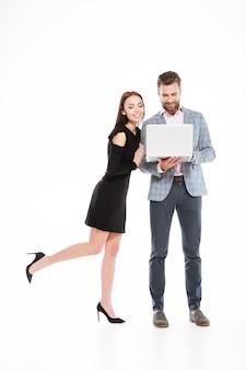 Jovem alegre casal apaixonado usando computador portátil.