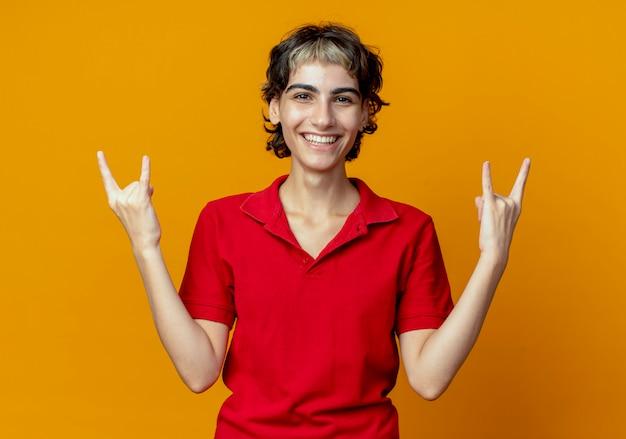 Jovem alegre caucasiana com corte de cabelo de duende fazendo sinais de pedra isolados em um fundo laranja