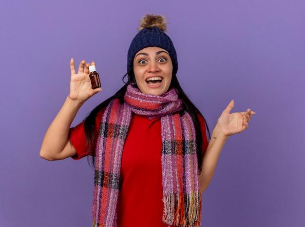 Jovem alegre caucasiana doente com chapéu de inverno e lenço segurando medicamento em vidro apontando para o lado isolado na parede roxa