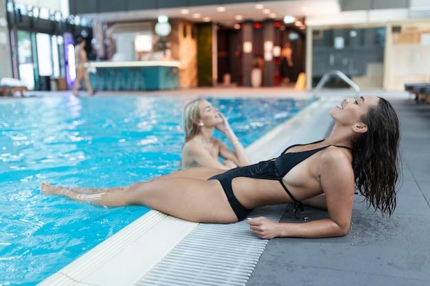 Jovem alegre caucasiana em traje de banho gosta de um dia no centro de spa, enquanto cochila entre as sessões de sauna e piscina.