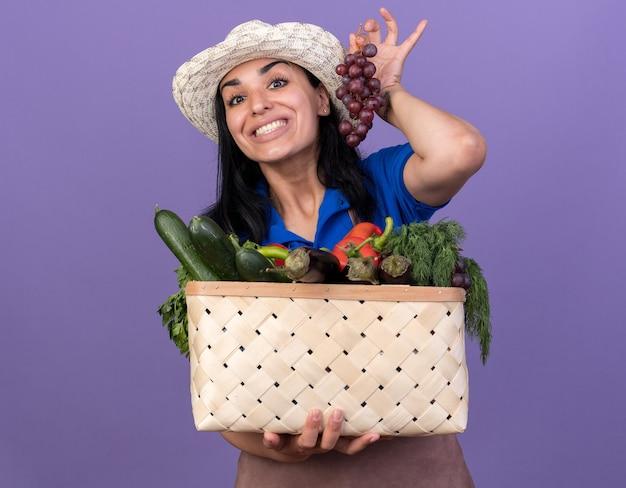 Jovem alegre caucasiana jardineira vestindo uniforme e chapéu segurando uma cesta de legumes e cacho de uva isolado na parede roxa