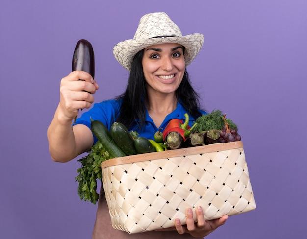 Jovem alegre, caucasiana, jardineira, vestindo uniforme e chapéu, segurando uma cesta de legumes estendendo a berinjela em direção à câmera, isolada na parede roxa