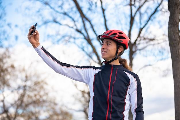 Jovem alegre ciclista masculina no sportswear e capacete tomando selfie em smartphone no parque