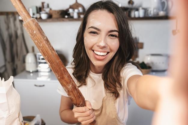 Jovem alegre coberta de farinha tirando uma selfie na cozinha, segurando o rolo de massa