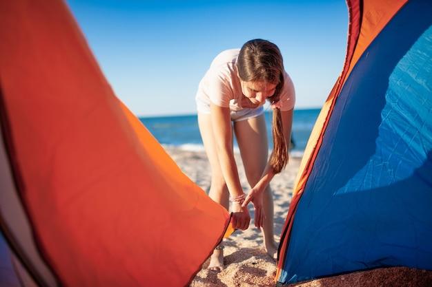 Jovem alegre com a morena fecha uma tenda brilhante olhando para suas ações cautelosas na costa do mar azul em uma bela noite