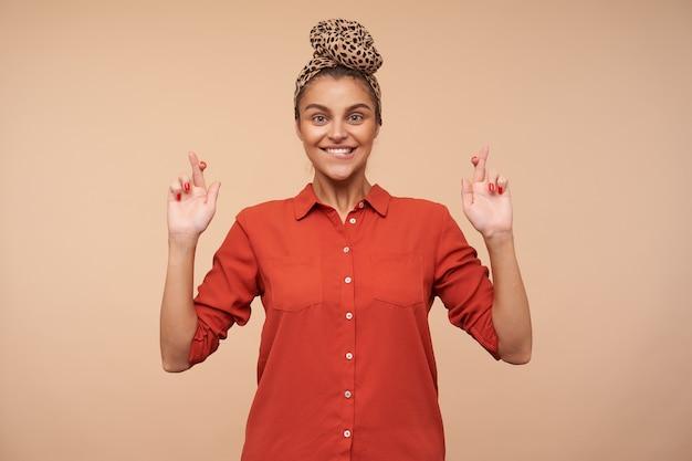 Jovem alegre com cabelos castanhos e maquiagem natural, mordendo o lábio inferior e cruzando os dedos para dar sorte enquanto fica de pé sobre uma parede bege com uma camisa vermelha