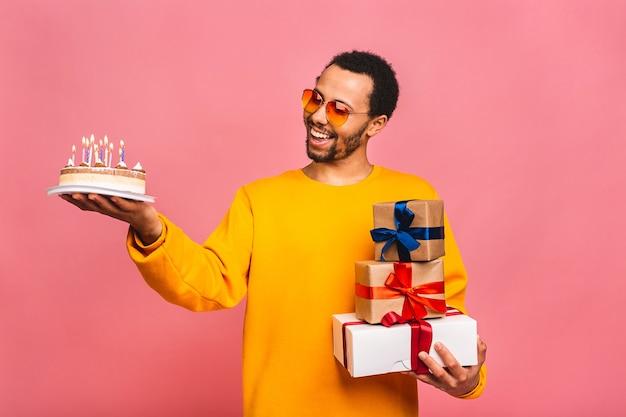 Jovem alegre com caixas de presente, soprando velas em um bolo de aniversário isolado em rosa.