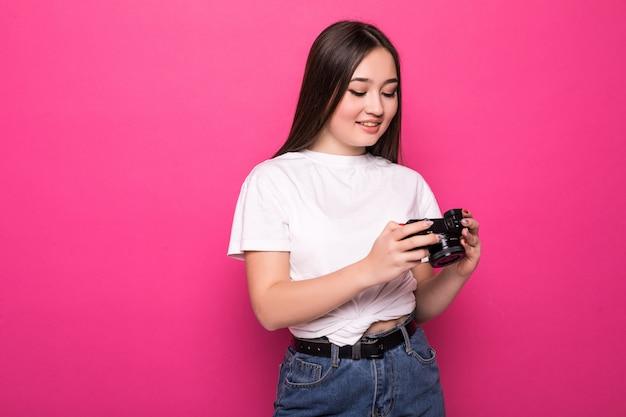 Jovem alegre com câmera fotográfica na parede rosa