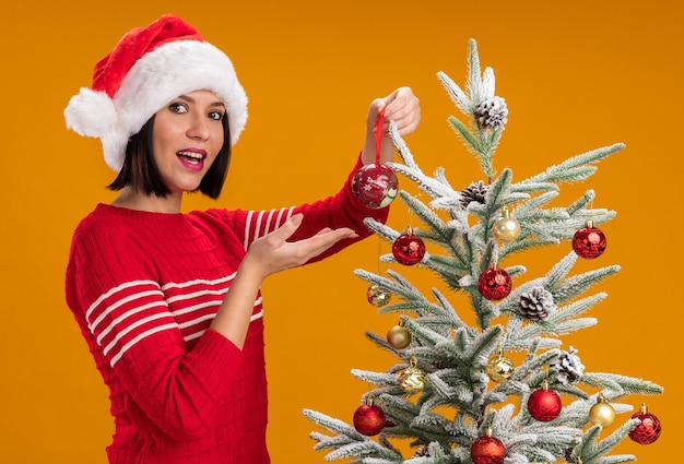 Jovem alegre com chapéu de papai noel em pé em vista de perfil perto da árvore de natal, decorando com enfeites de natal olhando para a câmera apontando para bugiganga isolada em fundo laranja