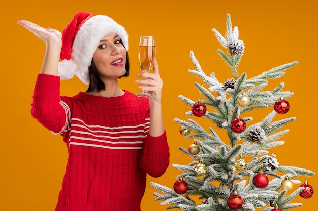 Jovem alegre com chapéu de papai noel em pé perto da árvore de natal decorada, segurando uma taça de champanhe, olhando para a câmera, mostrando a mão vazia isolada em um fundo laranja