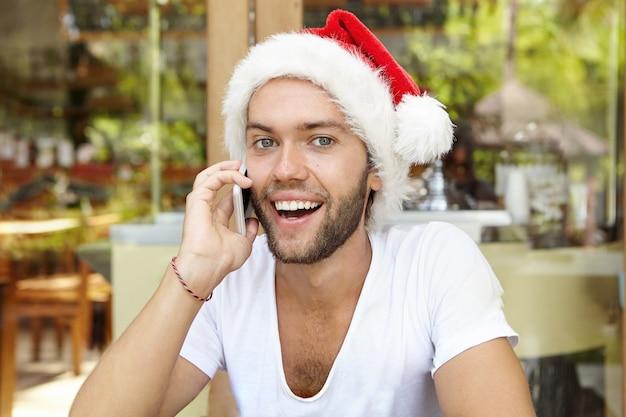 Jovem alegre com chapéu de papai noel vermelho e sorrindo alegremente enquanto conversa ao telefone