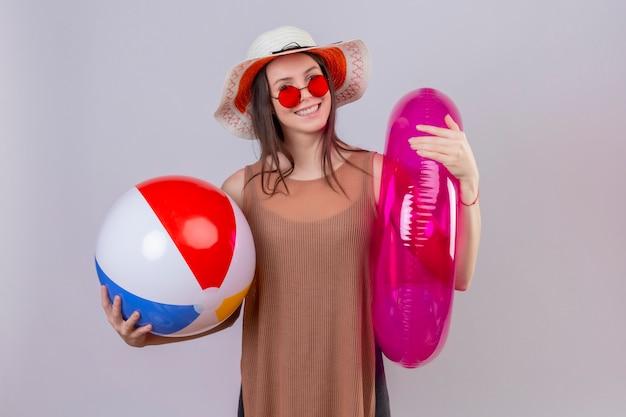 Jovem alegre com chapéu usando óculos escuros vermelhos segurando uma bola inflável e um anel sorrindo em pé no branco