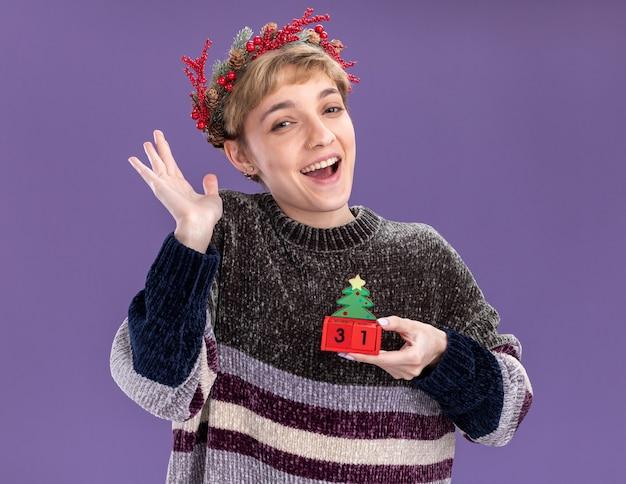 Jovem alegre com coroa de flores na cabeça, segurando o brinquedo da árvore de natal com data, olhando para a câmera, mostrando a mão vazia isolada no fundo roxo