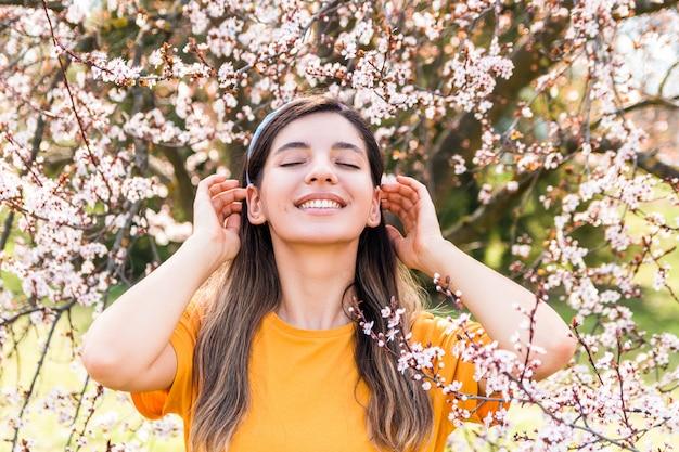 Jovem alegre com os olhos fechados, apreciando o início da primavera contra a árvore frutífera com flores cor de rosa no parque