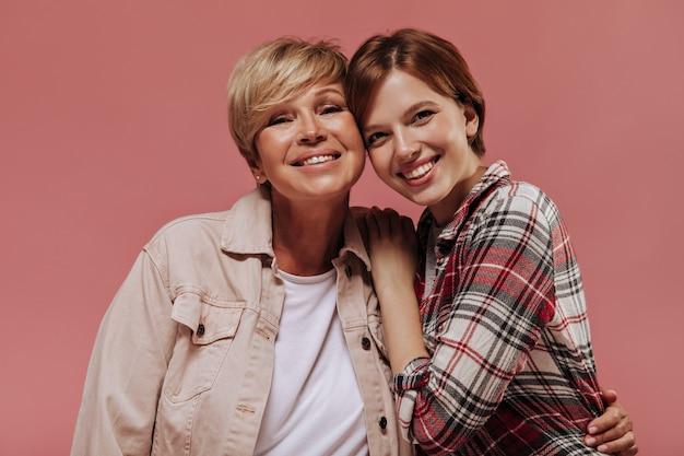 Jovem alegre com penteado curto em camisa xadrez, olhando para a câmera e sorrindo, juntamente com uma mulher loira de jaqueta bege no fundo rosa.