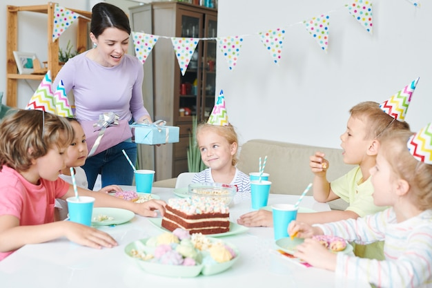 Jovem alegre com presentes de aniversário ao lado da mesa com um grupo de crianças e fazendo lembranças na festa em casa