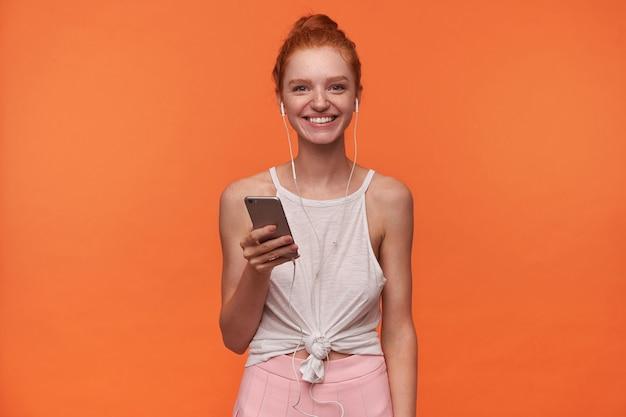 Jovem alegre com seu cabelo sexy em um nó usando fones de ouvido, ouvindo música em seu smartphone, olhando para a câmera com um sorriso largo e encantador, isolado sobre um fundo laranja em roupas casuais