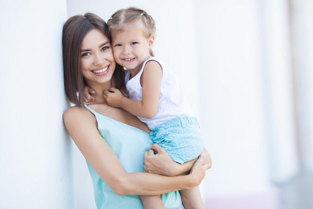 Jovem alegre com sua filha ao ar livre. família feliz junto no verão. mãe e filho abraçando.