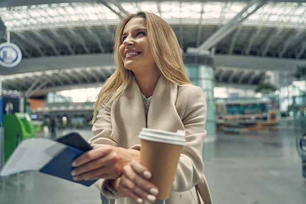 Jovem alegre com um sorriso no rosto enquanto olha para o monitor de chegadas e partidas